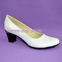 Белые кожаные туфли на устойчивом каблуке.
