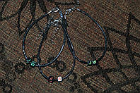 браслет из вощеного шнура с 2 бусинами с буквами на черном фоне