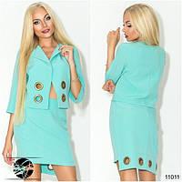 Стильный комплект: пиджак и юбка, декорированные большими люверсами. Пиджак без застежки. Юбка сзади на молнии