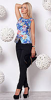 Женский брючный костюм: черные брюки + синяя блуза с цветочным рисунком.