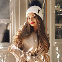 Вязаная женская шапка с бубоном из меха с брошью. Цвет белый с темно-синим.