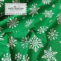Новогодняя ткань с крупными снежинками на зеленом фоне № 865