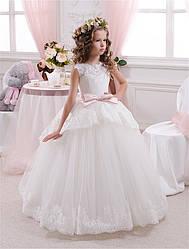 Платье кремовое длинное без рукава с розовым поясом.