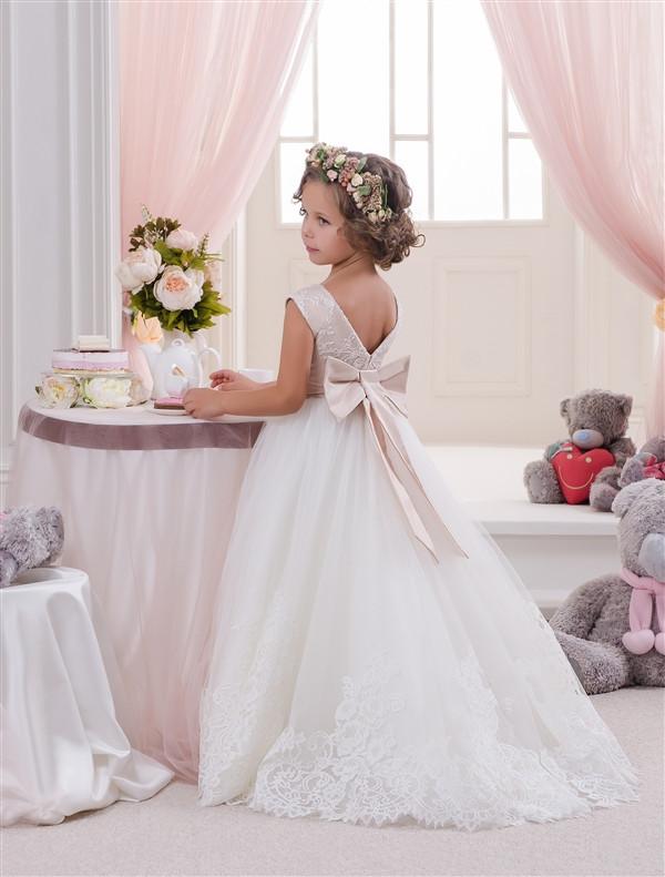Платье кремовое длинное без рукава с большим бантом сзади.