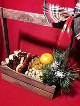 Дерев'яний ящик з фруктовим наповненням і хвоєю.
