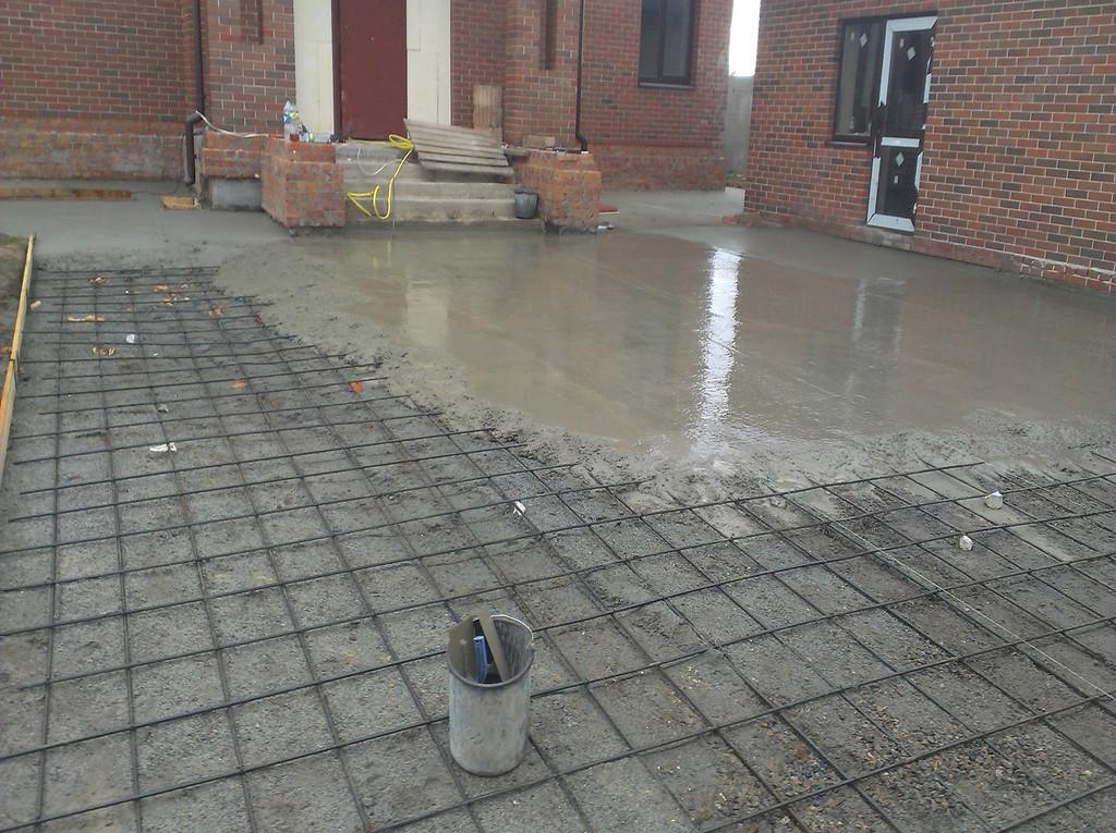 Подготовительные работы уже выполнены, грунт снят, щебень и отсев уплотнены, арматура связана, начался сам процесс заливки бетона.