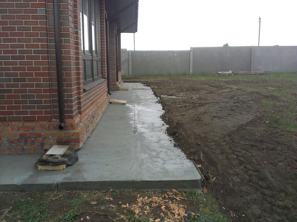 """Цокольная часть фасада благоразумно ещё не подвергалась чистовой отделке, дабы не быть испорченной при проведении """"грязных"""" бетонных работ."""