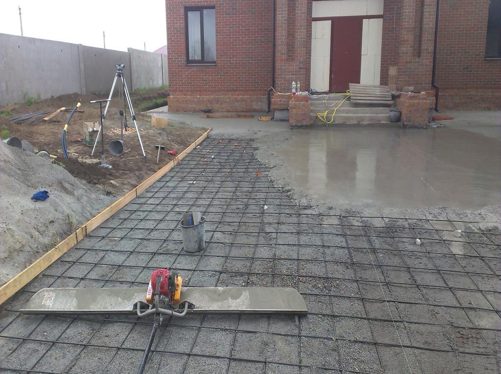 Перед укладкой бетона (точнее, перед началом работ по планировке) вся территория была размечена с помощью нивелира. Бетон принимался по ниткам. Точность в пределах 10 мм (ввиду того, что сверху будет тротуарная плитка).