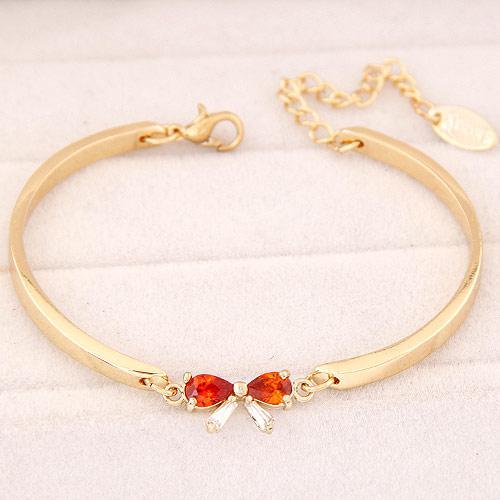 Браслет тонкий Бантик под золото с красным камнем B004472