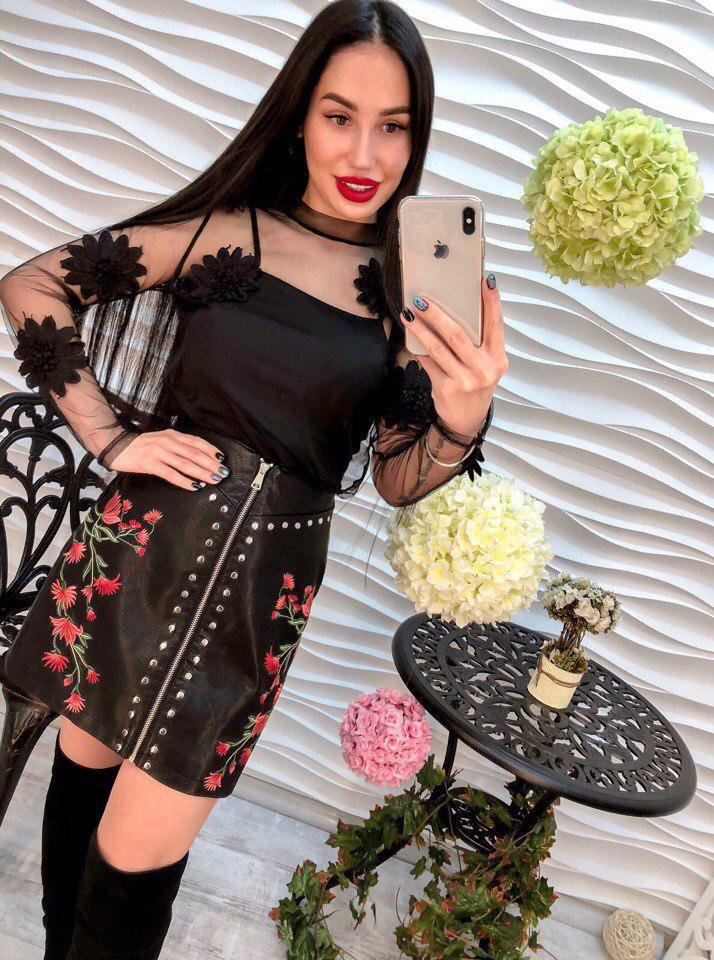 Красивая женская блуза декорирована аппликацией в виде цветов