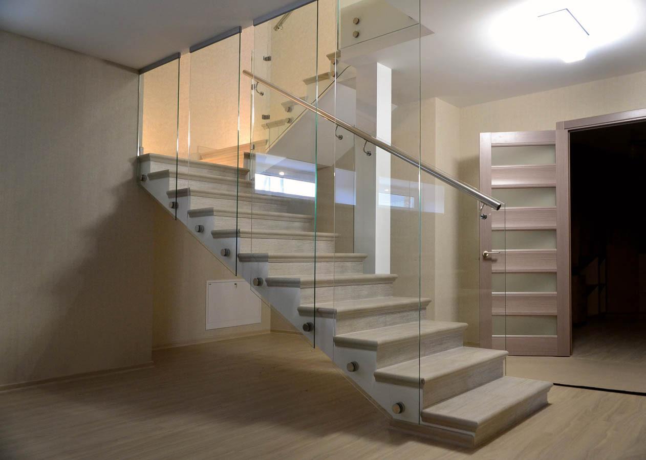 Оригинальное ограждение из стекла на лестнице выполнено полосами шириной 600 мм под потолок
