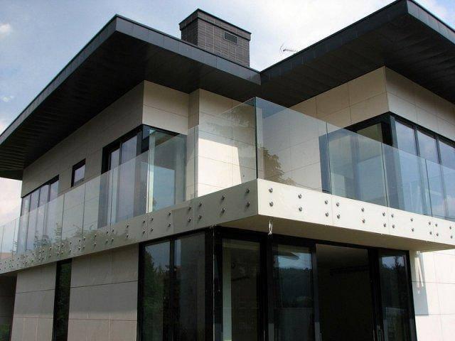 Ограждение балкона второго этажа из прозрачного стекла, установленное на круглые коннекторы из нержавейки