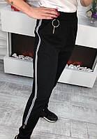 Женские брючки в спортивном стиле с лампасами и металлическим брелком.