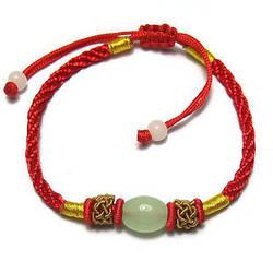 Браслет Красная нить с нефритовой бусиной и золотыми плетениями.