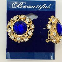 Серьги гвоздики с синим камнем в золотой ажурной оправе
