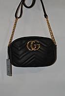 Небольшая чёрная сумка Gucci с золотистой цепочкой застегивается на молнии.