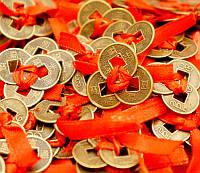 Три монеты перевязанные красной нитью треугольником