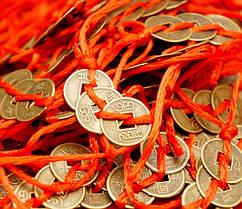 Три монеты перевязанные красной нитью в линию