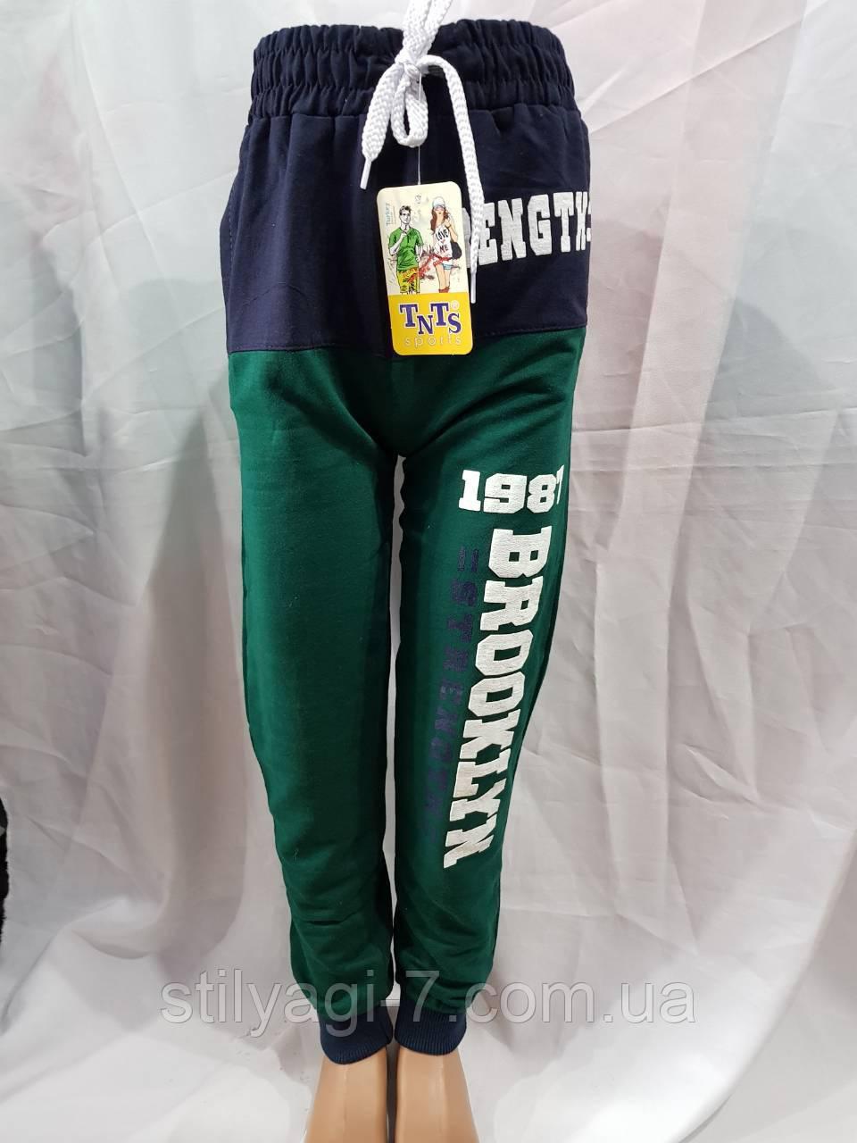 Спортивные штаны для мальчика-подростка на 13-16 лет зеленого цвета на манжете с надписью оптом