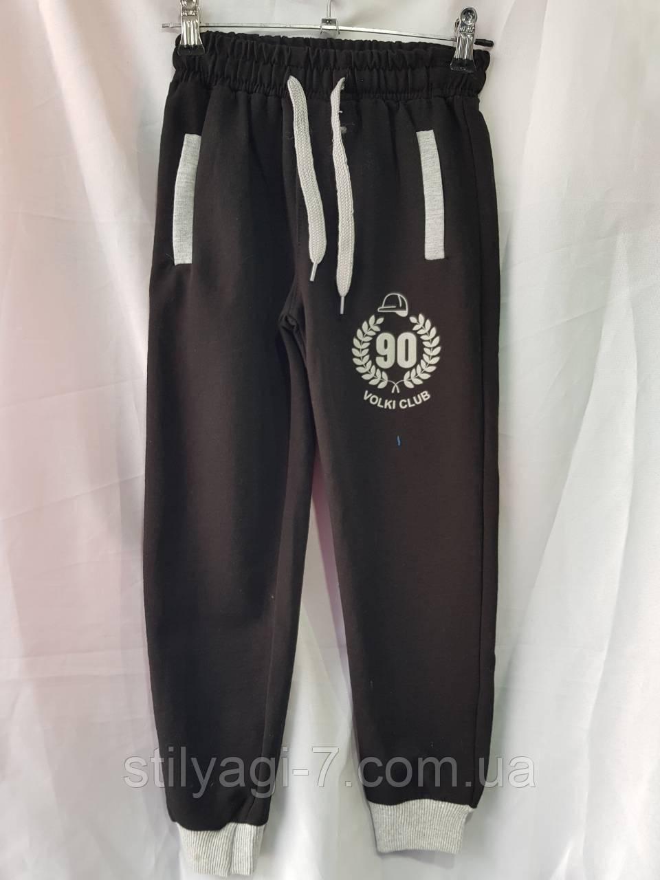 Спортивные штаны для мальчика-подростка на 9-12 лет черного цвета на манжете с надписью оптом