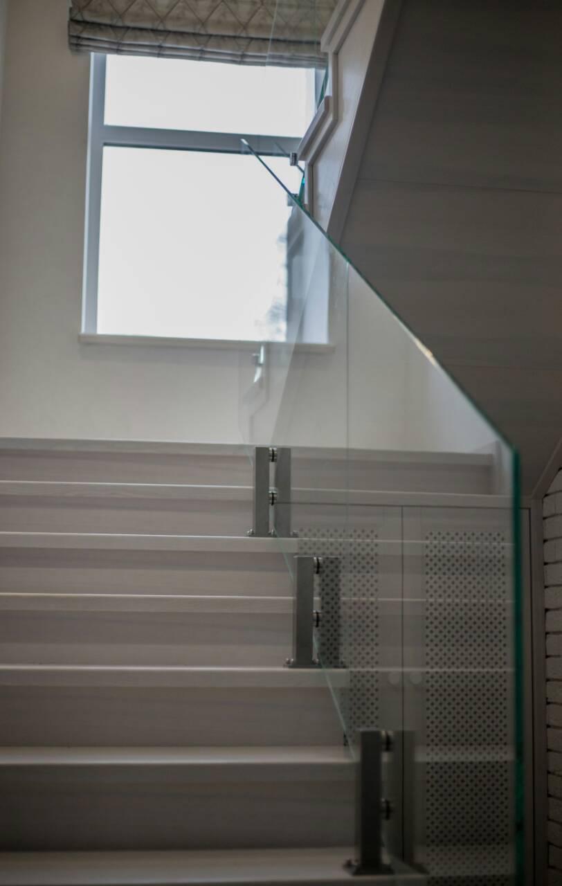 Стеклянное ограждение лестницы на маленьких стойках из нержавейки и каленного стекла диамант 12 мм