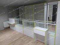 Вариант мебели для аптеки выполнен в белом цвете с оливковой окантовкой, на стеклянных прилавках установлена воздушно капельная защита из стекла в раме из хромированной трубы