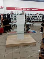 Стеллаж островной или стеклянная горка для магазина обуви. Стеллаж имеет основание под основной цвет мебели в магазине и белого цвета колону на которой размещены стеклянные полки для демонстрации обуви. Стеклянные полки цельные, все крепления скрыты