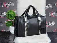 Черная женская кожаная сумка в виде бочонка с декоративными цепями.