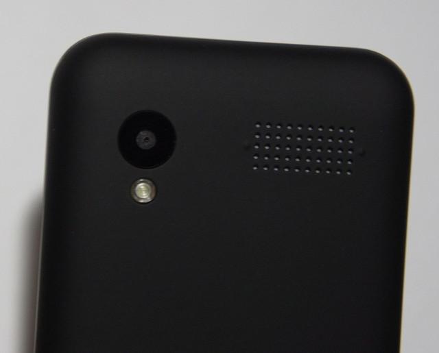 На тыльной стороне корпуса расположен достаточно крупный и мощный динамик, камера 0,3 МП со вспышкой, которую можно использовать в качестве фонарика