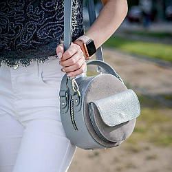 Круглая женская сумка из натуральной кожи и замши серого цвета.