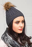 Темно-серая шапка в косы с енотовм помпоном