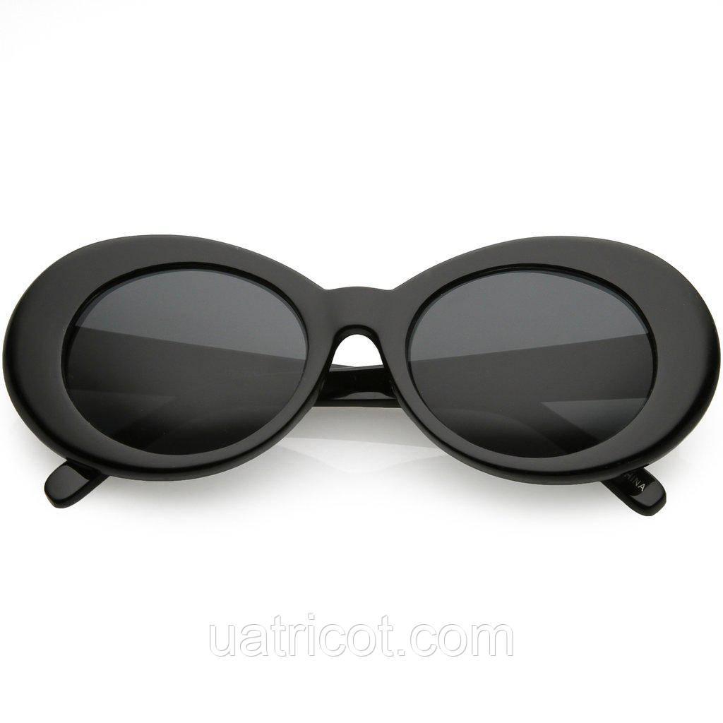 Большие овальные солнцезащитные очки в чёрной оправе с тёмными линзами