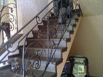 Дерев'яні сходи з кованими перилами