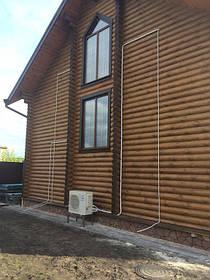 Наружный блок мультисплит-системы кондиционера установлен на деревянном доме типа сруб.