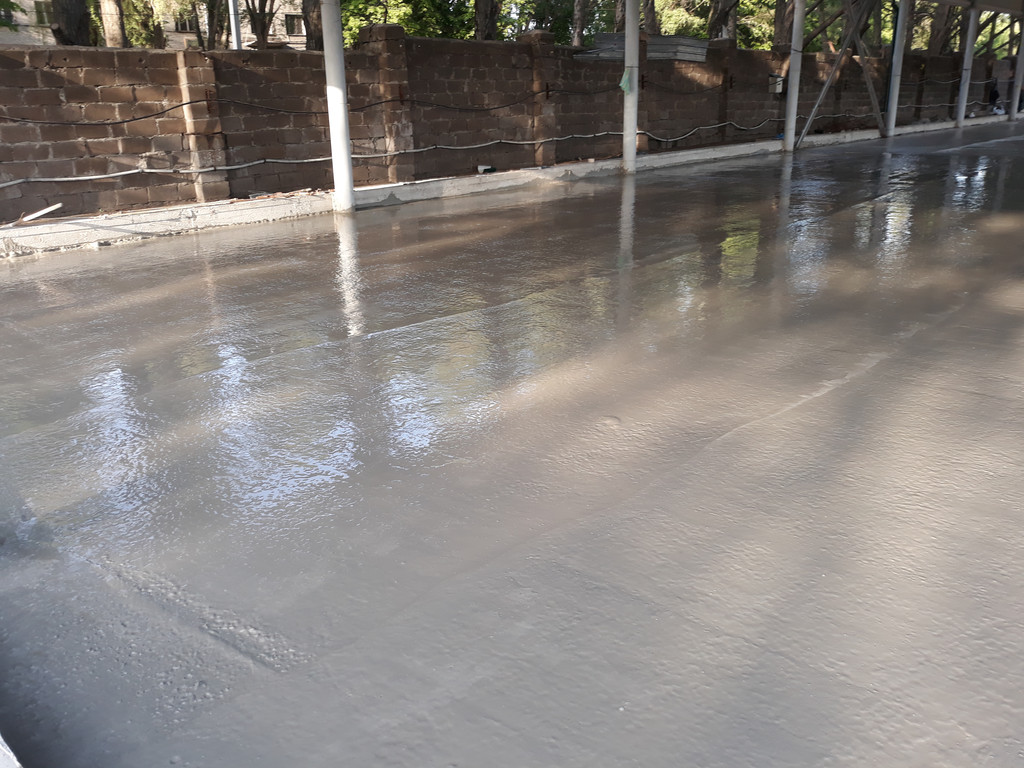 После укладки бетона с помощью плавающей виброрейки.
