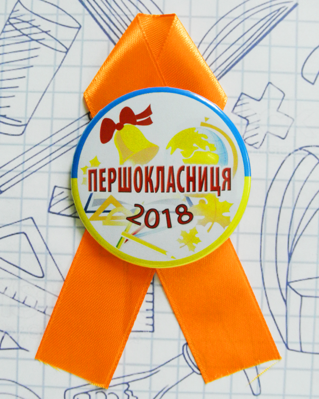 """Закатной значок круглый """"Першокласниця"""" на оранжевой ленточке"""