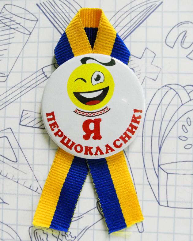 """Закатной значок круглый """"Я першокласник"""" на сине-желтой ленточке"""