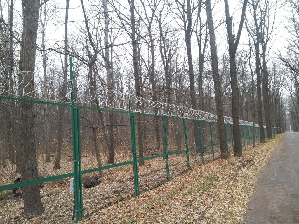 Установка колючей проволоки на забор из сетки рабица