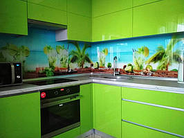 Установленное скинали с фотопечатью. Зеленые фасады кухни органично приняли рисунок стеклянного фартука.