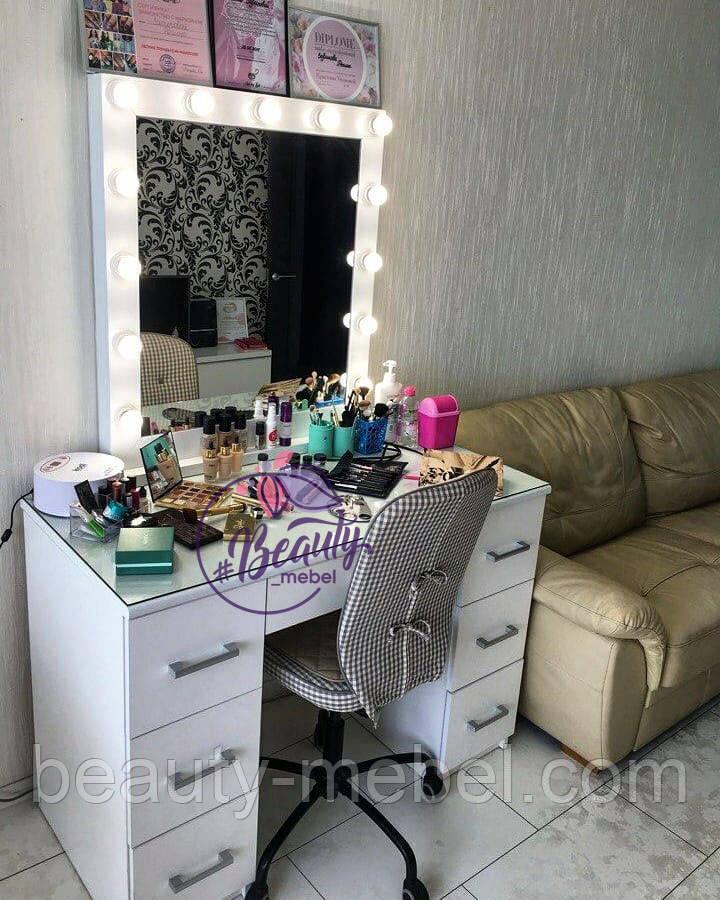Профессиональный гримерный стол с большим количеством ящиков и зеркалом с лампами.