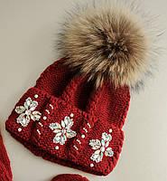 """Шикарная женская шапка крупной вязки со стразами и большим бубоном из енота """"Эльза"""""""
