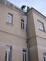 Удаление сосулек с крыши альпинистами