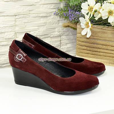 Женские замшевые туфли бордового цвета на невысокой танкетке, декорированы ремешком