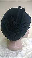 чёрная шапка с двумя выпуклыми складами украшенная ажурным цветком