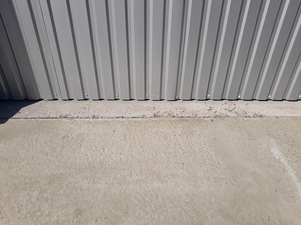 Место стыка бетонной дороги и пола ангара.