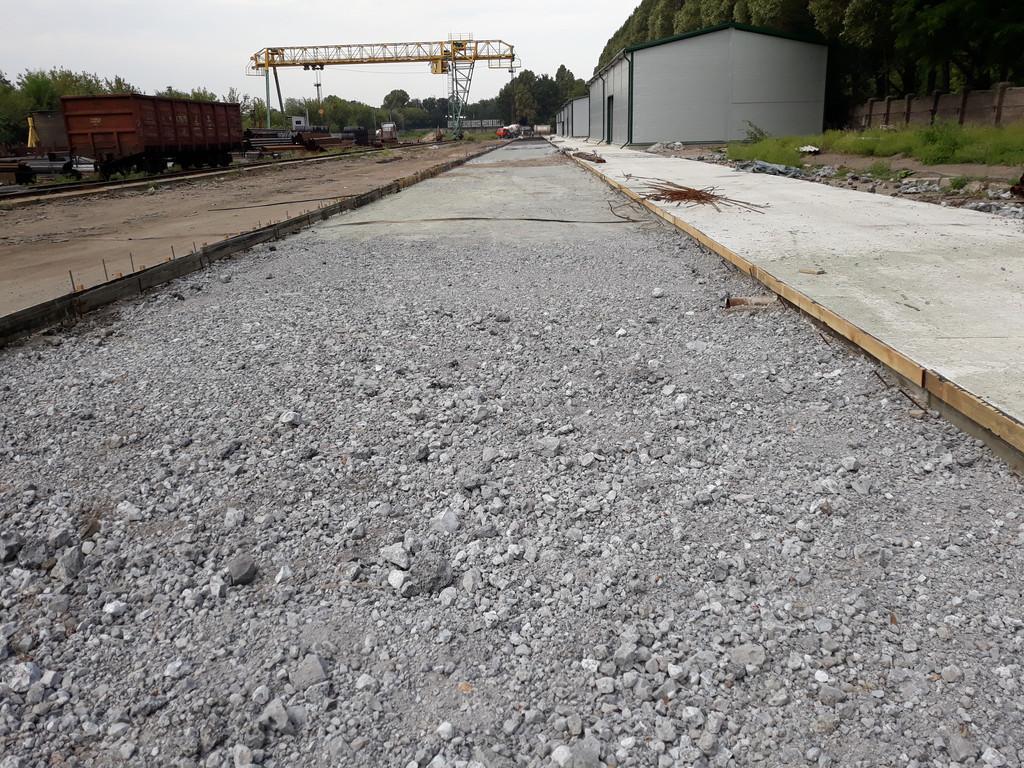Укатанный катком отвальный шлак, выравнивающий слой отсева, плёнка, арматура, 200 мм бетона.