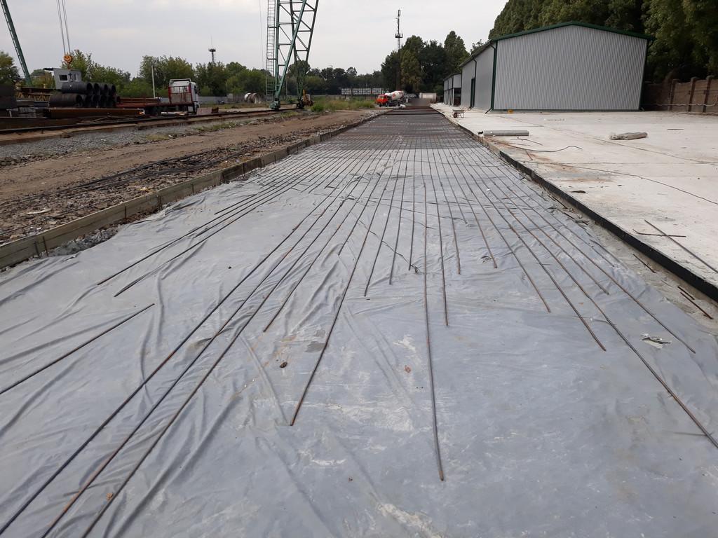 Пока на ближней части дороги проводятся работы по устройству армирующего каркаса, на дальней уже принимается бетон.
