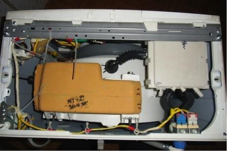 Вид стиральной машинки, после того как вы сняли крышку. Оранжевый предмет - это противовес.