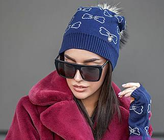 Женская зимняя вязаная шапка с митенками и бубоном из меха енота пряжа софт темно-синего цвета