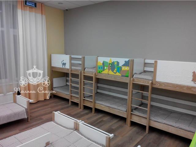 """Спальня соединяет в себе двухъярусные и низкие кровати, благодаря чему можно разместить наибольшее количество детей. Кровати оформлены в тематике """"Городок""""."""